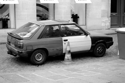 Typically French. No two panels match, covered with dents, different wheels, and parked illegally on a traffic cone.