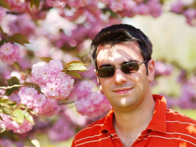 Matthew poses in front of the cherry blossoms